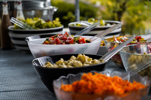 C'est un buffet de salades froides contenues dans des bols noirs ou transparents. Il y a une salade contenant des tomates et chaque plat a une cuillère pour pouvoir se servir