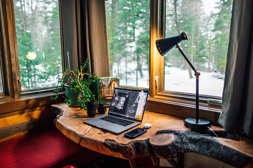 Wooden desk beneath a large window with laptop plant and lamp on