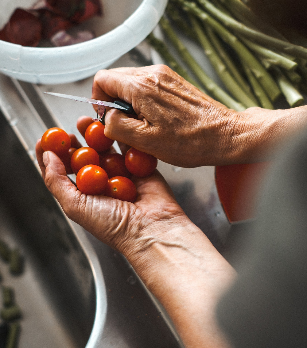 person holding tomatoes and knife with cooking materials and food in background