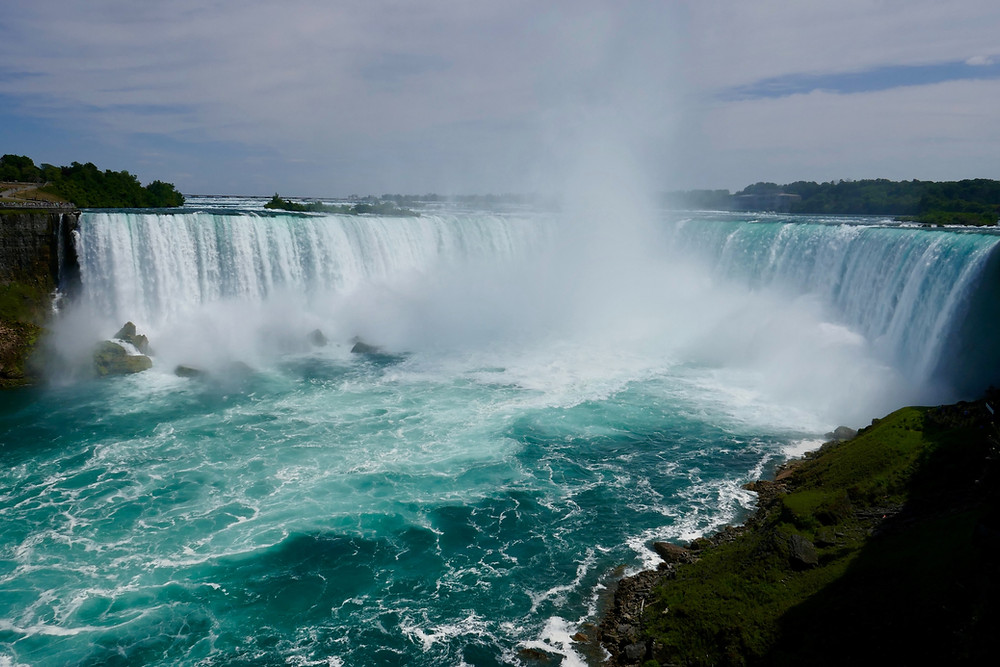 pounding water and mist from Niagara Falls seen from the Canadian side