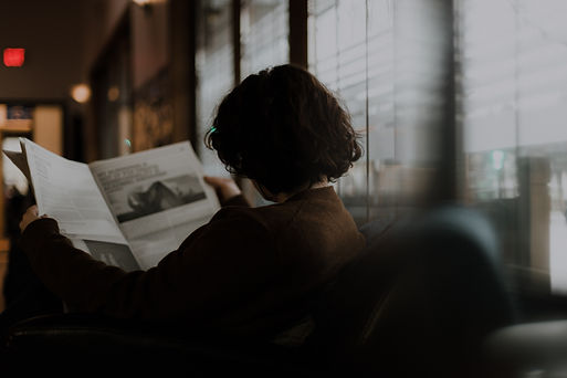 Woman with brown hair reading newspaper