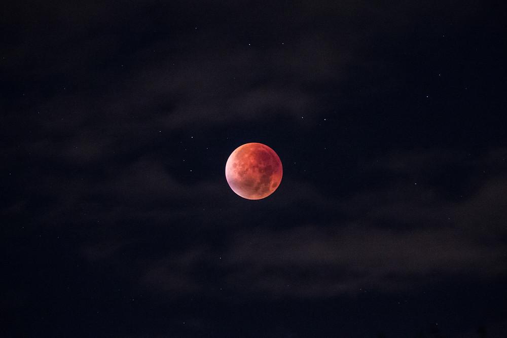 Dark nights sky with the red full moon illuminated