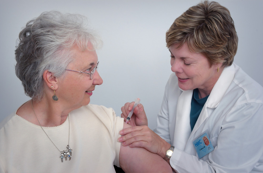 A doctor takes blood from an older woman.