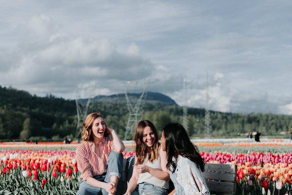 ผู้หญิงสามคนกำลังนั่งคุยภาษาอังกฤษกันในทุ่งดอกไม้
