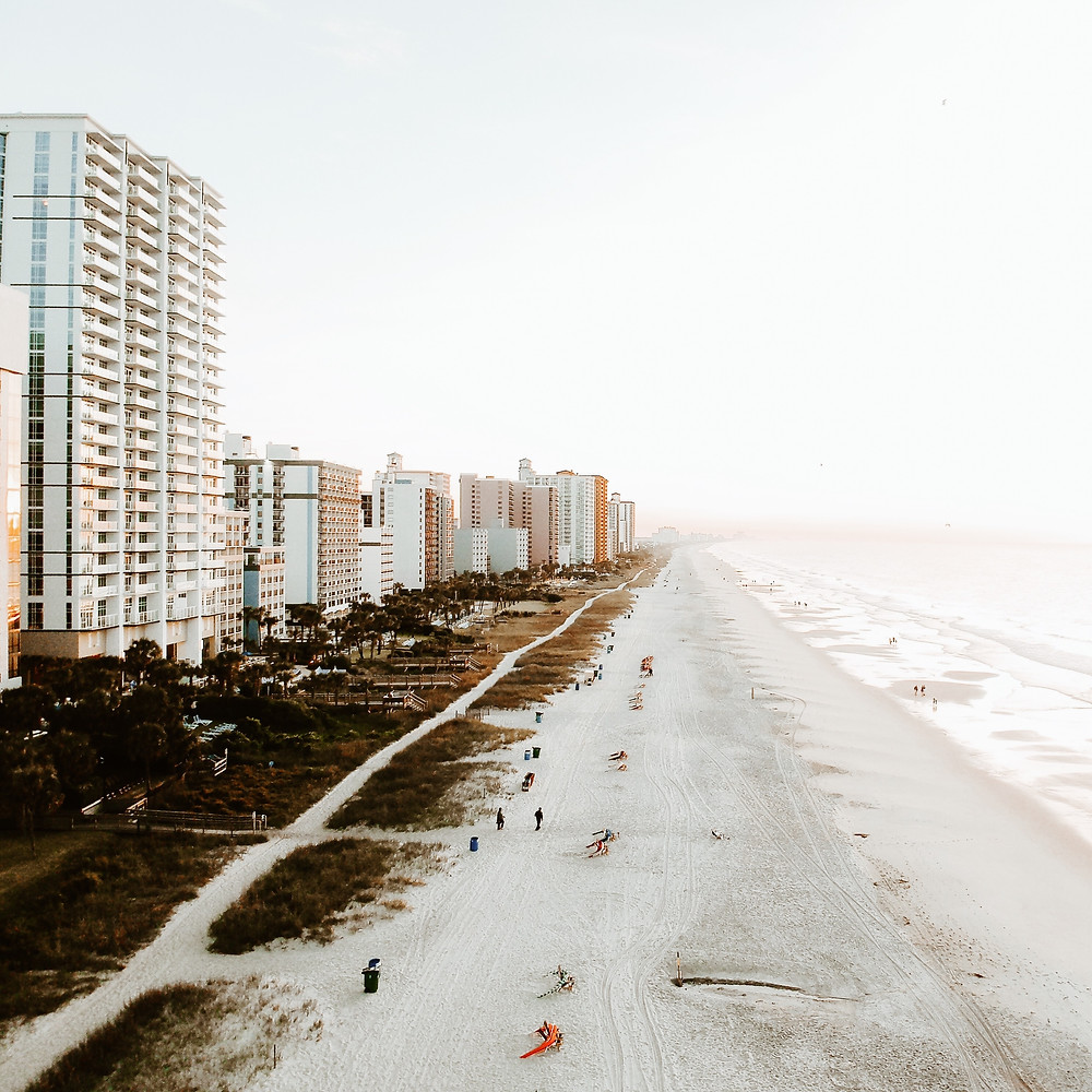 Tall rise buildings with people on the beach at Myrtle Beach