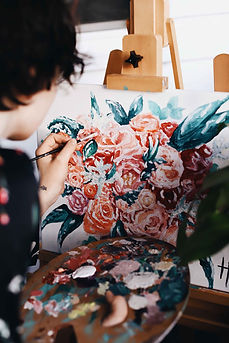 Looking over a painter's shoulder at a canvas with roses being painted on it