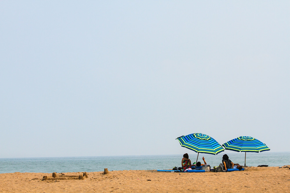 guarda-sóis na praia com pessoas relaxando