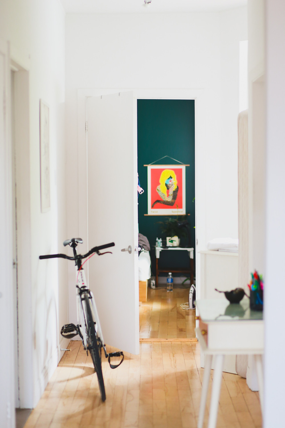 A bright entry hallway with which walls and wooden floors. A deep forest green wall is poking through one of the doorways with a vibrant, pop-art style art piece. There is a black and white bicycle leaning on the wall and a small hall table which has a few decorative pieces placed on top.