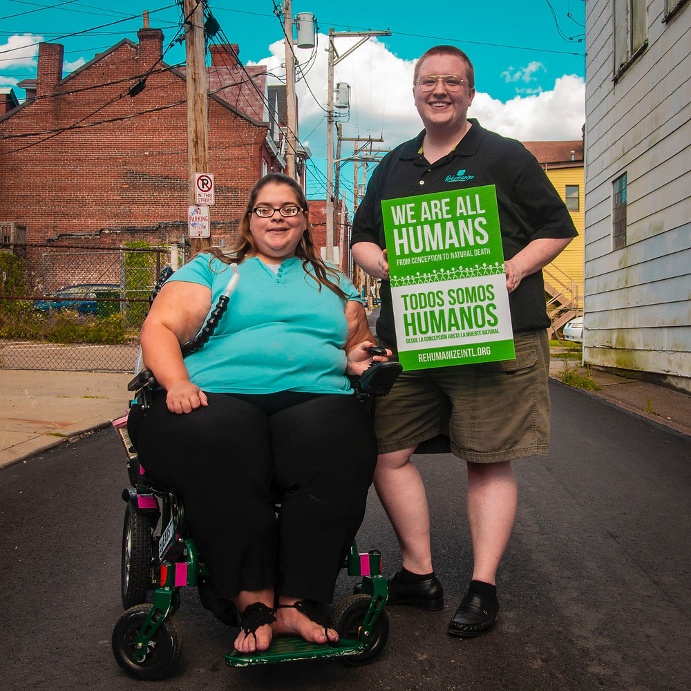 "A picture with a female in a wheelchair, and a man standing next to her; he is holding a sign that reads ""we are ALL humans""."