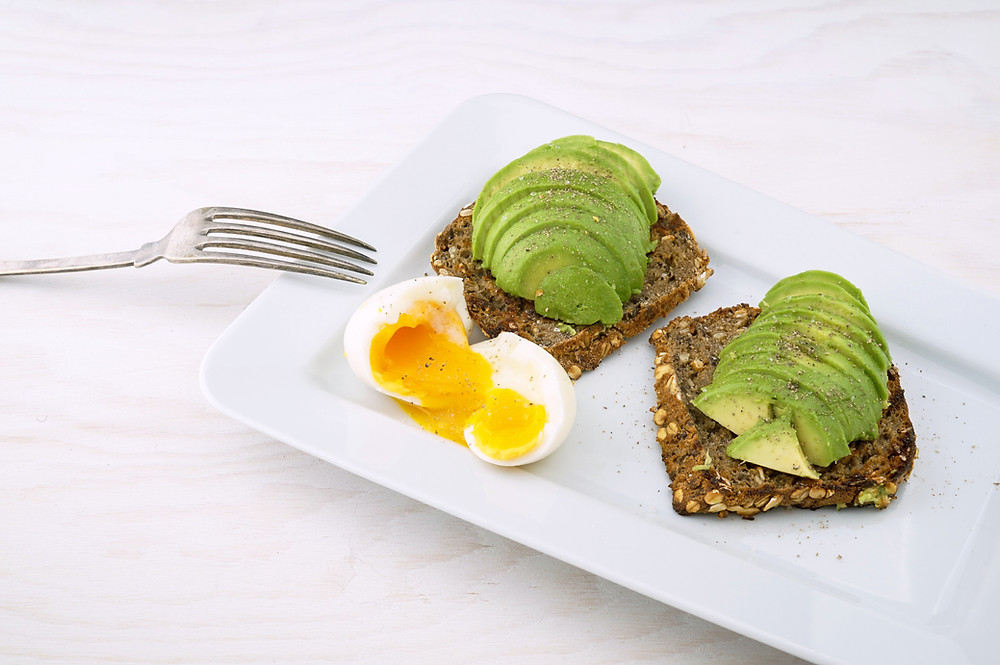 Soft boiled egg and sliced avocado on rye bread