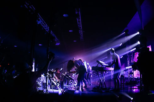 A behind the scenes picture of an indie band performing live on stage. The band has over 5 musicians and the view of the band is from the side curtain, demosntrating a typical day in the life of a tour manager.