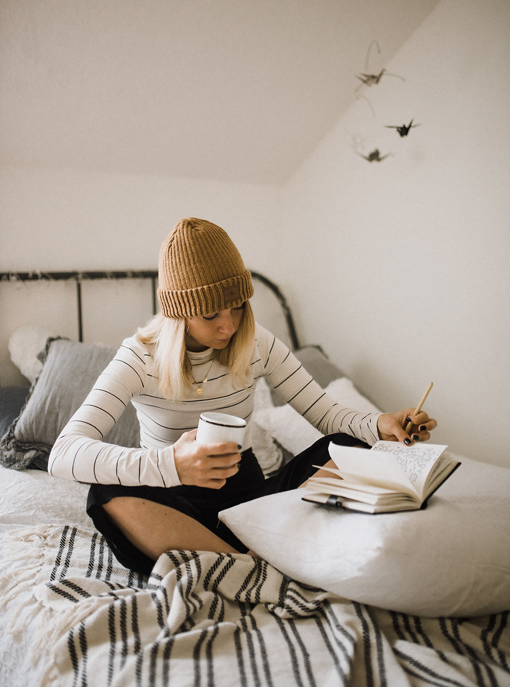 woman in beanie writing in diary in white bedroom