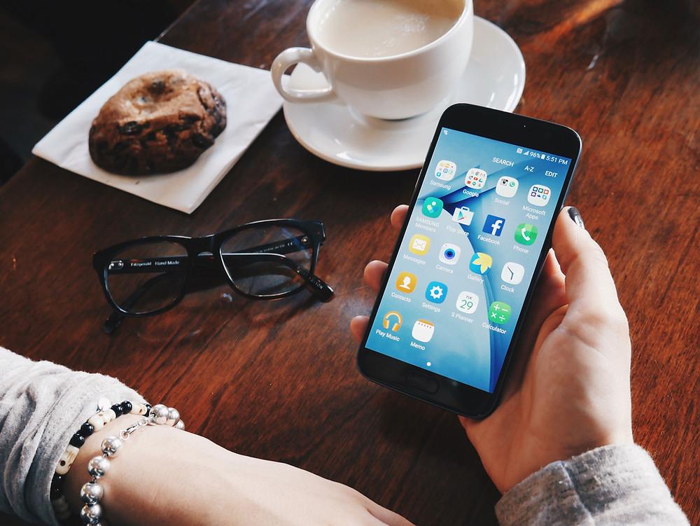 girl holding phone, glasses, coffee