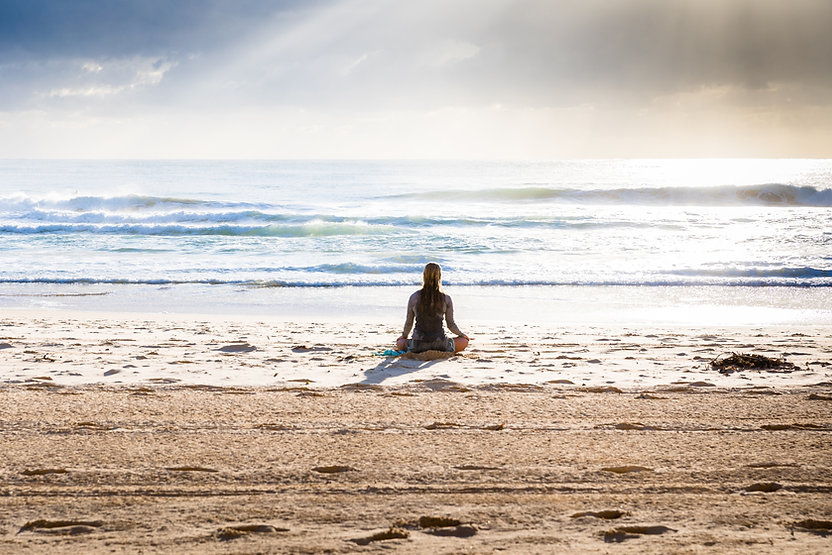 Woman sitting cross legged on the beach with her hands on her knees