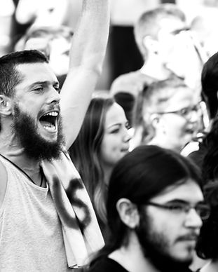 A man screams while holding up a sign at a protest.