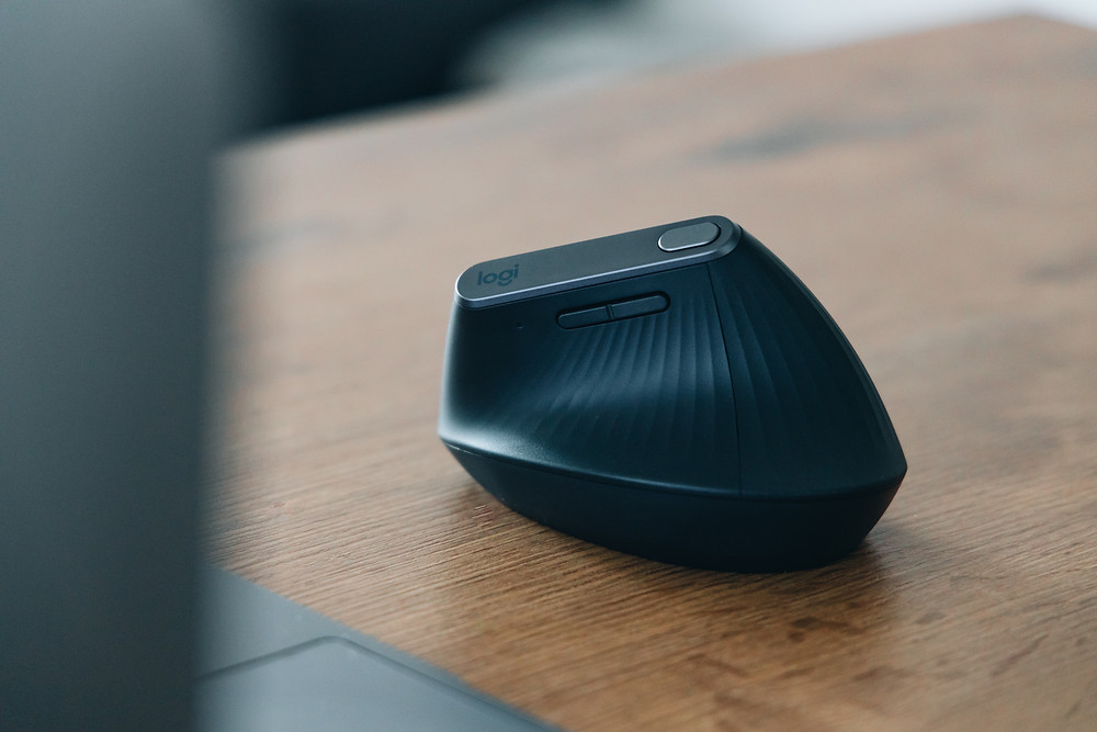A logitech vertical mouse standing on a wood table.