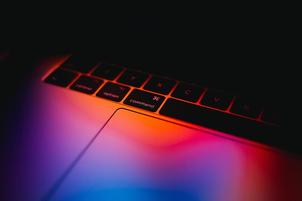 Macbook keyboard with a rainbow light.