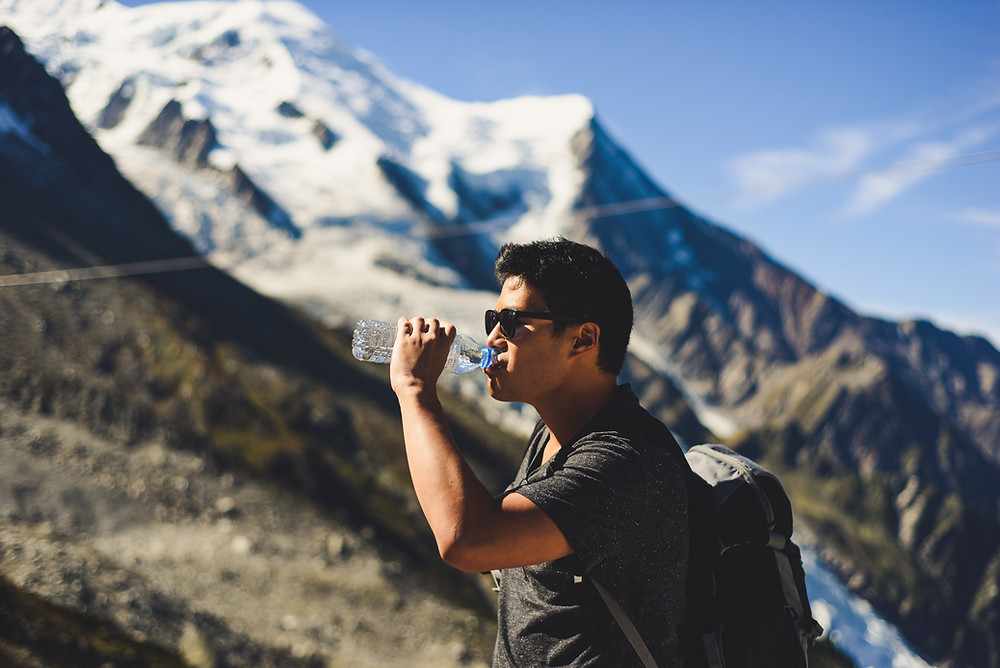 Man drinking bottled water in the mountains
