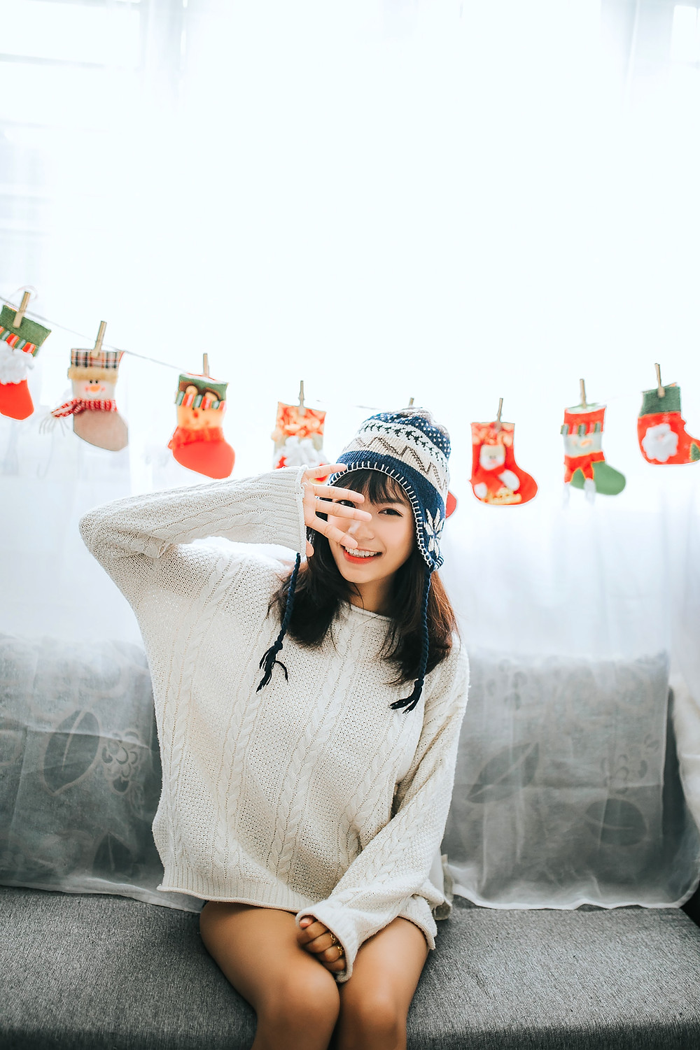 Cute woman sitting wearing a christmas hat and jumper with christmas decorations behind her