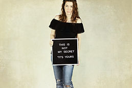 Image by Jen Theodore A woman holding a sign.