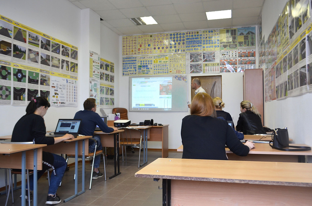ครูผู้ชายกำลังสอนภาษาอังกฤษนักเรียน 5 คนในห้อง