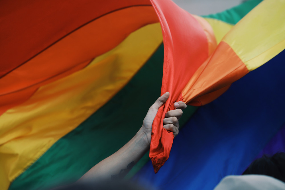 Picture of a man holding the red and orange parts of a rainbow flag which floats in the background.