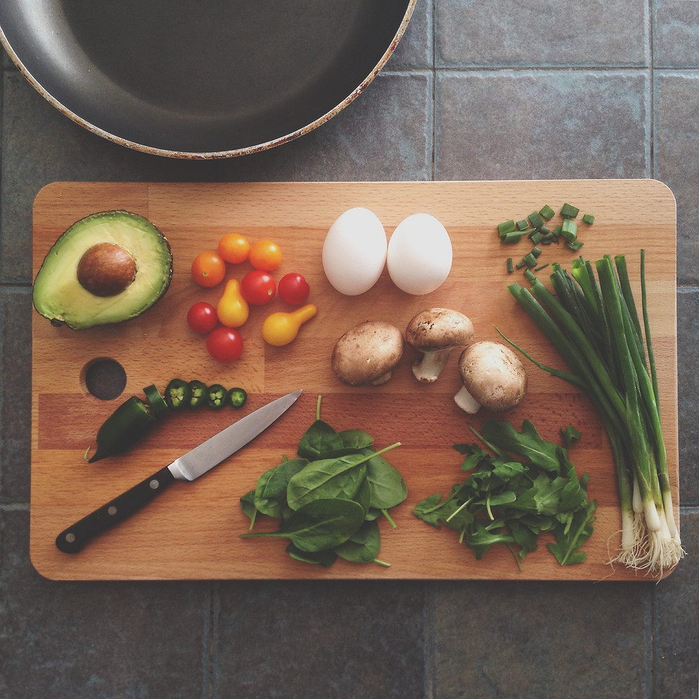 Cutting board with fruit, vegetables, and eggs