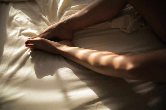 Image by Ava Sol of a womans legs in bed
