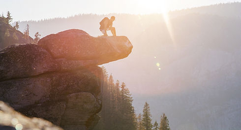 a man kneeling on a cliff edge during sunset.