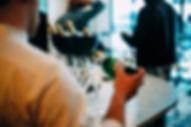 Tarjoilija tarjoilee kuohuviiniä tarjottimella kauniissa hääpaikassa Turussa.