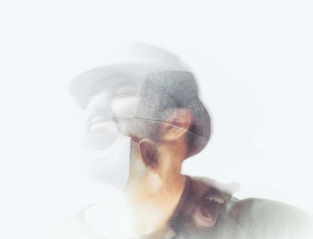 a person wering a hat who is covered in smoke blurring their face. You can see that they are both smilng and screaming, showing mental anguish from behind the smoke