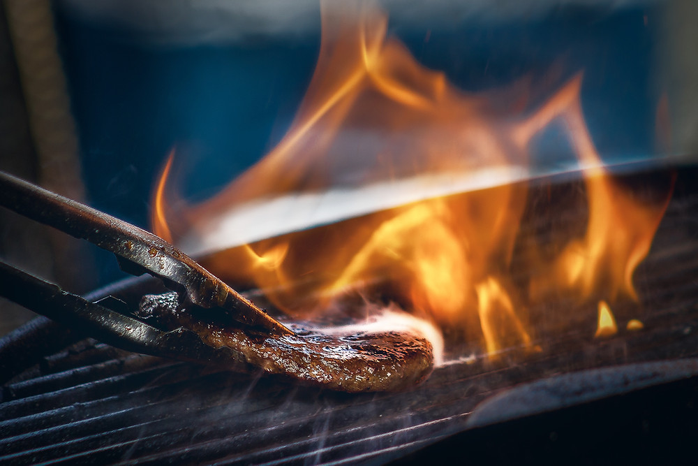 Metal tongs flipping over a piece of meat on a flaming BBQ