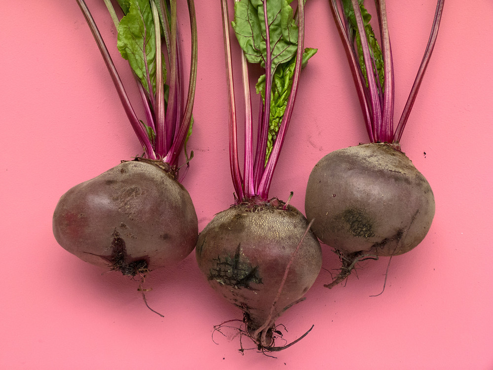 Three beets on a pink background