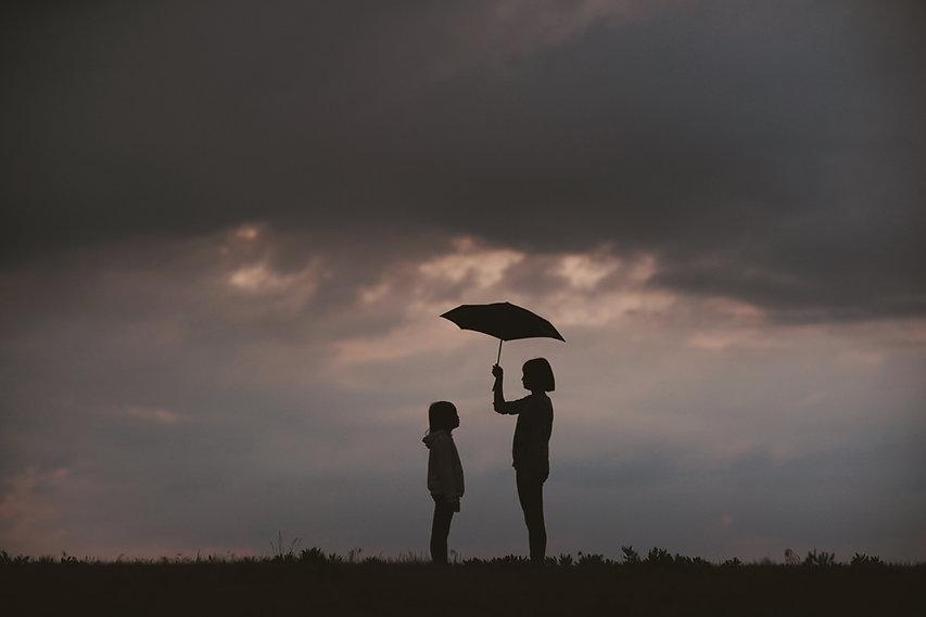 Two children holding an umbrella with dark sky background
