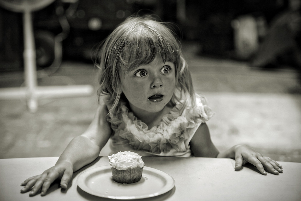 Young girl with surprised look and cupcake in front of her