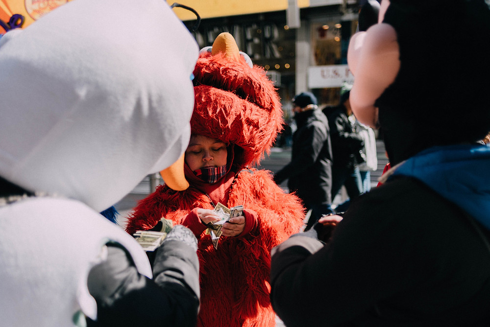 person dressed as elmo counting money