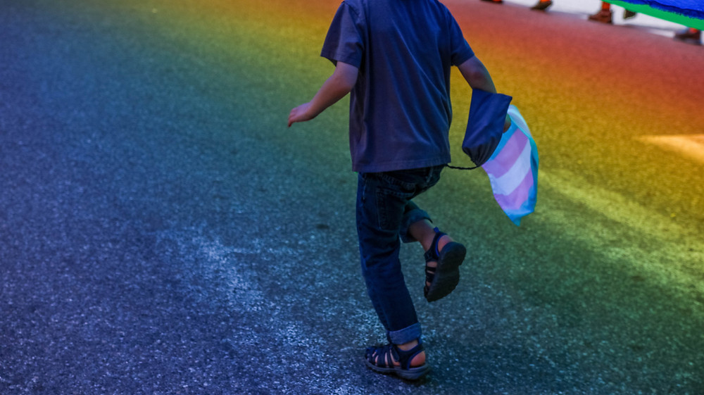 A child runs down a road painted in the rainbow pride flag. They hold a transgender pride flag in their hand.