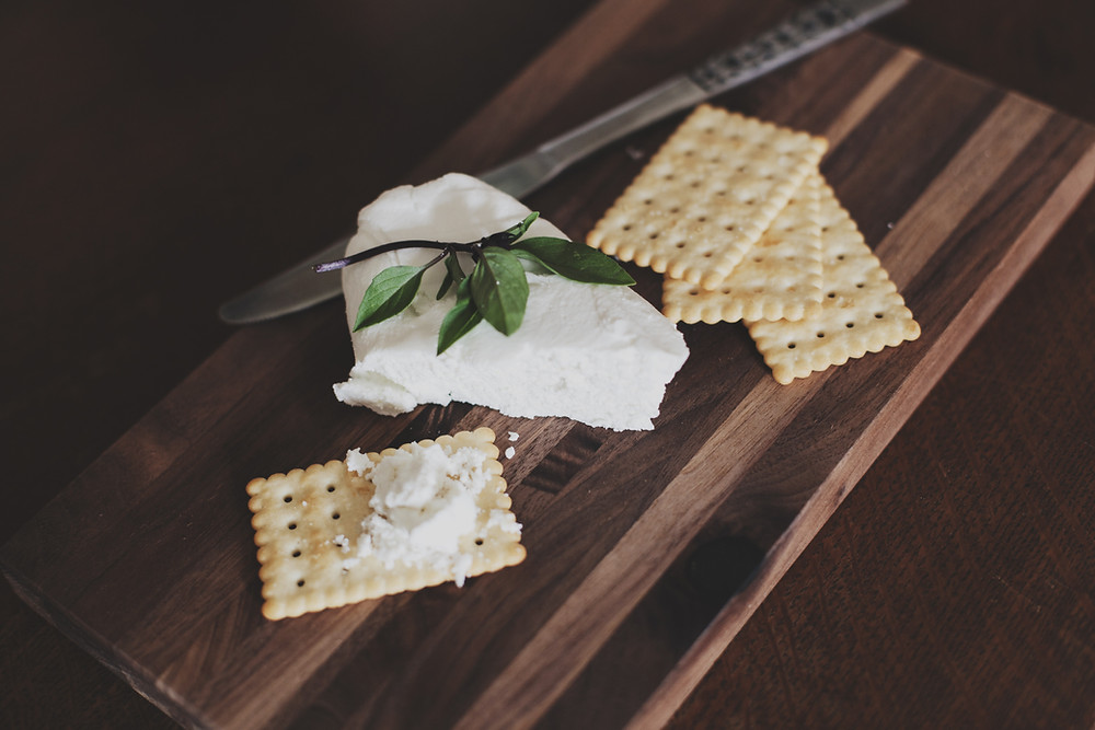 Creamy and soft cheese with herb and crackers atop a stained wooden cutting board beside a cheese knife