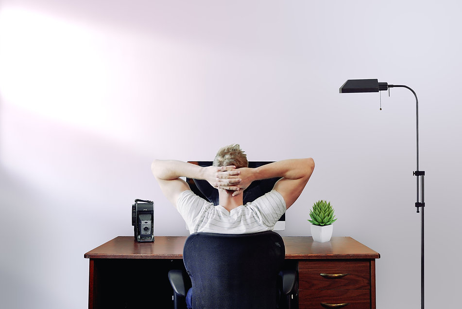 A man sitting at a desk facing the wall with his hands behind his head stretching his sore back. Image by Jason Strull.