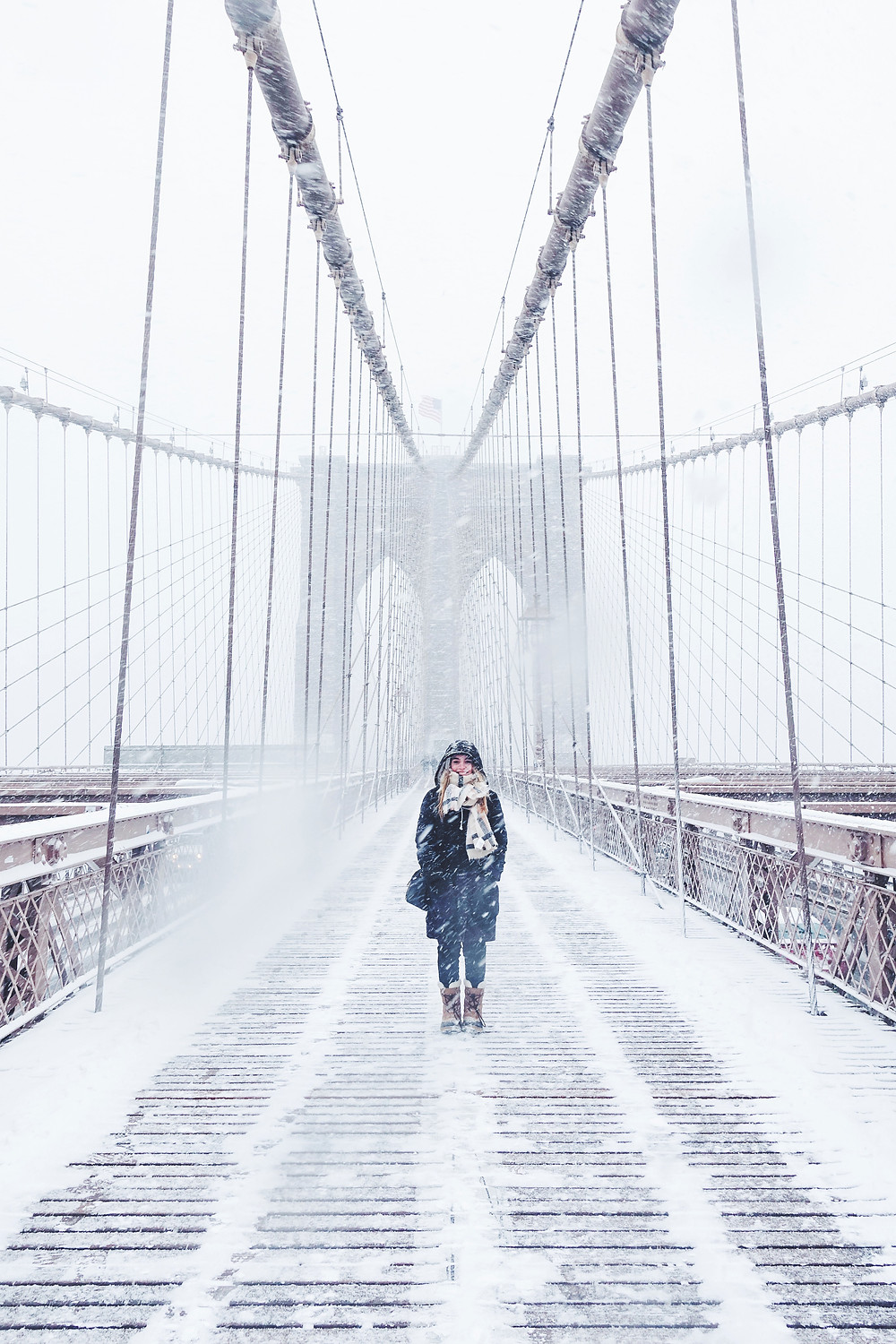 Woman walking on bridge covered in snow