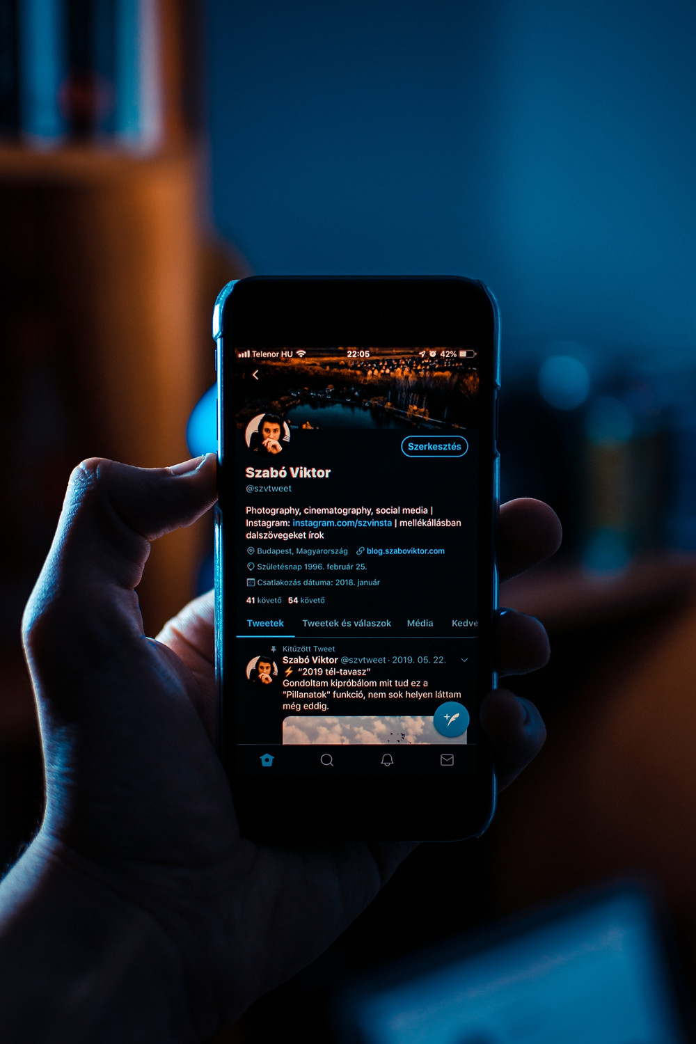 a man with phone having his twitter account opened