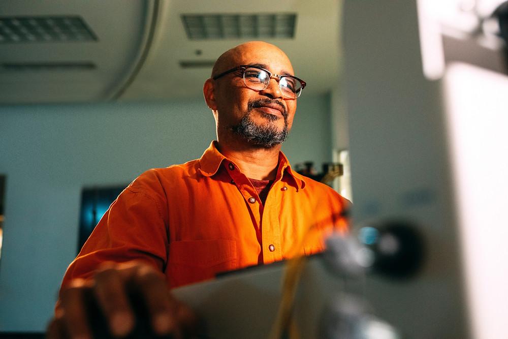 Homem de camisa laranja e óculos mexendo em computador