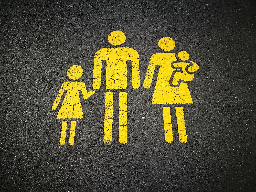 yellow sign on asphalt of a family, made out of basic shapes
