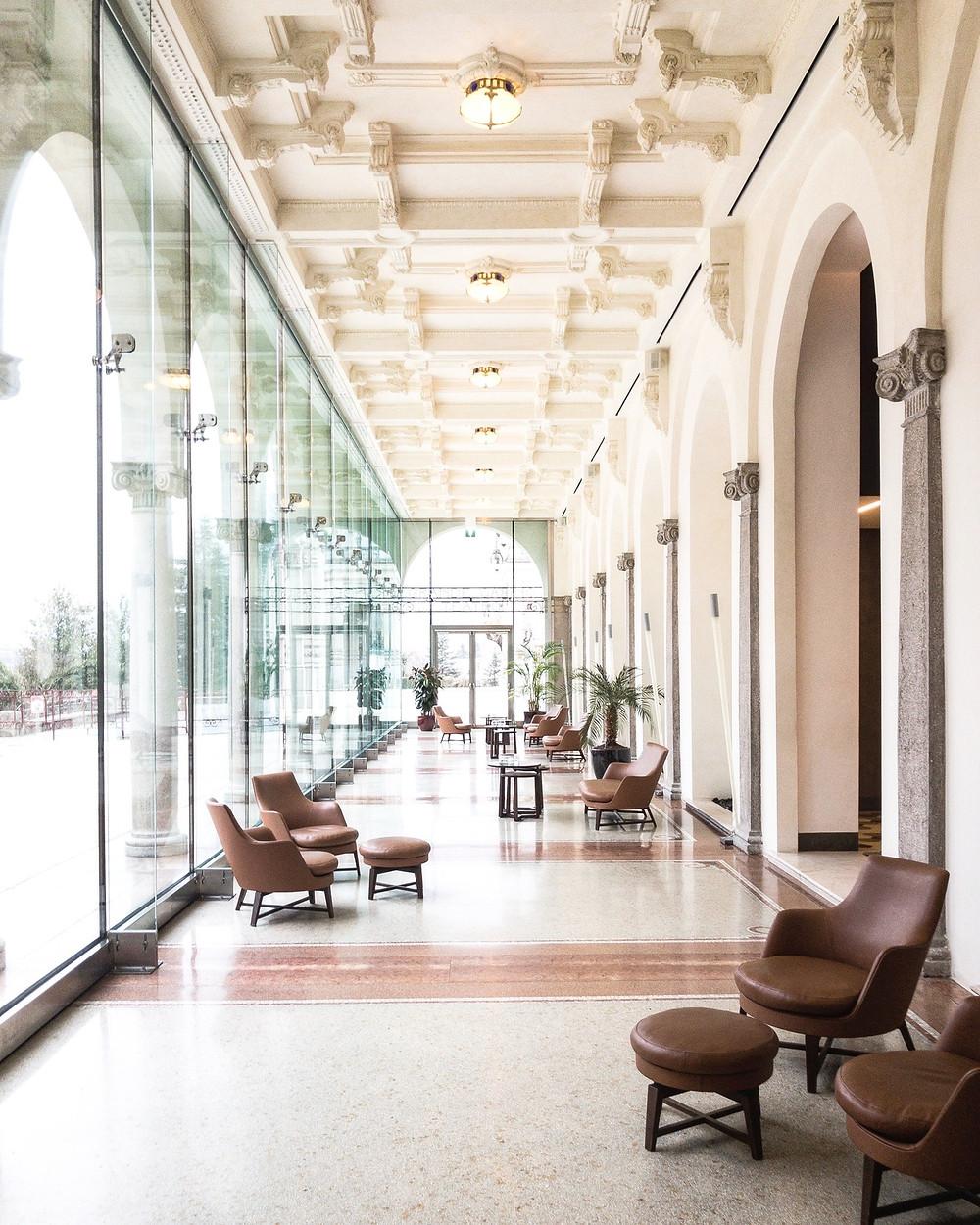 location matrimonio con soffitto alto bianco, vetrate e poltrone in pelle marrone