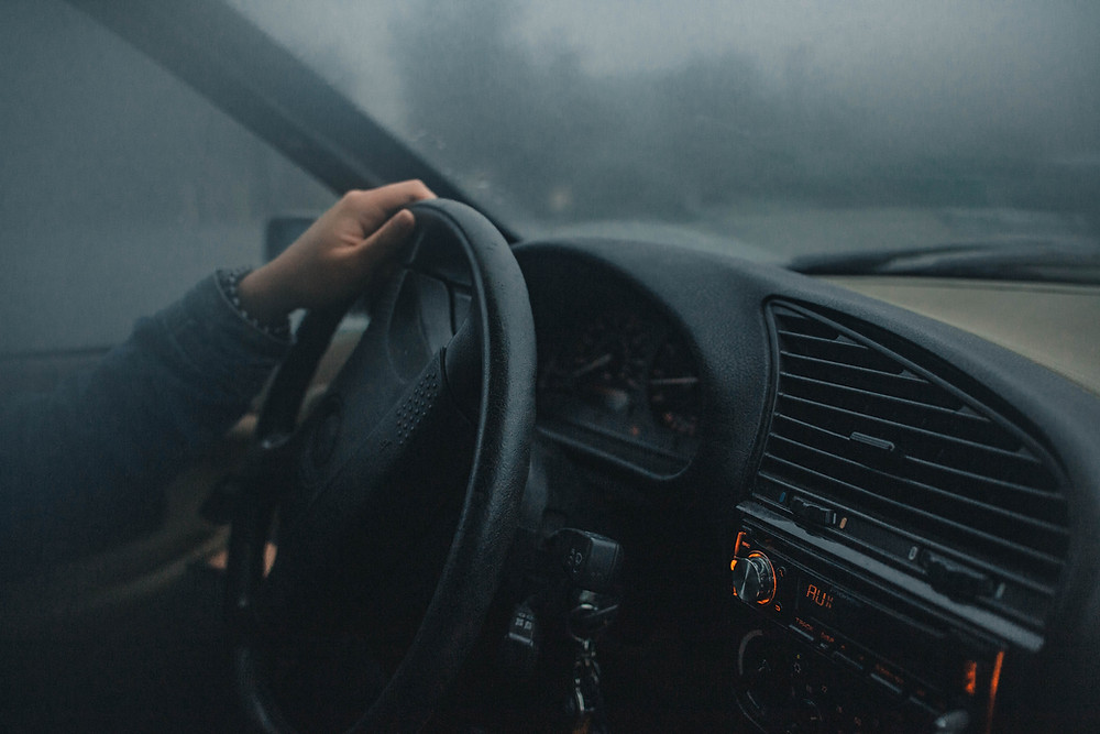 A driver holds the steering wheel on the inside of a car.