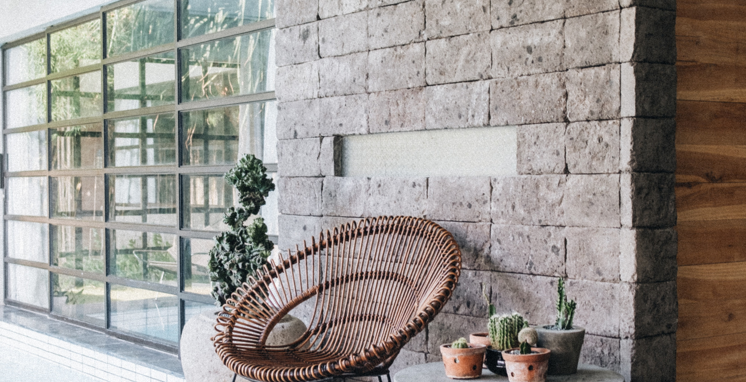Wicker Rattan Chair in Front of Brick Wall and Concrete Table with Catus