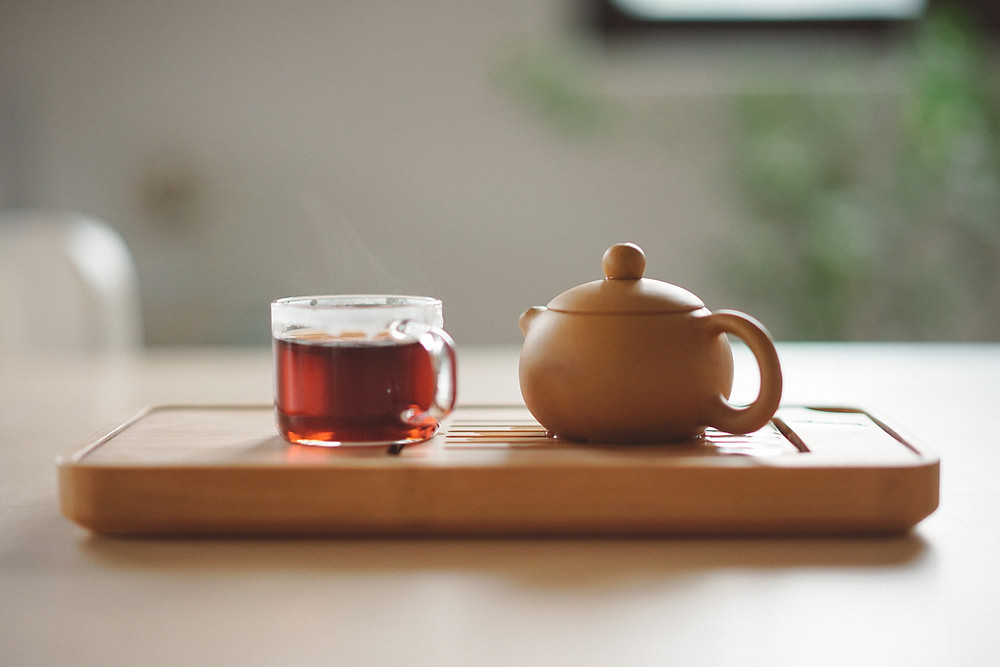 A small teapot and cup of tea sit on a tray in soft sunlight