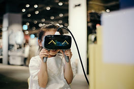 A child holds VR goggles in front of their face. Image by insung yoon