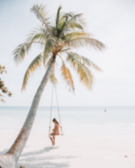 Girl sitting on swing on  beach next to a palm tree