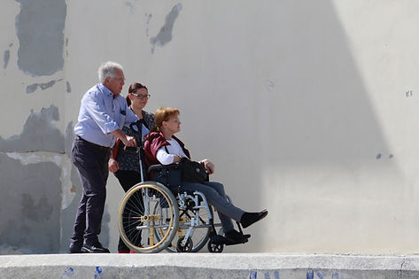 Man pushing woman in wheelchair outside